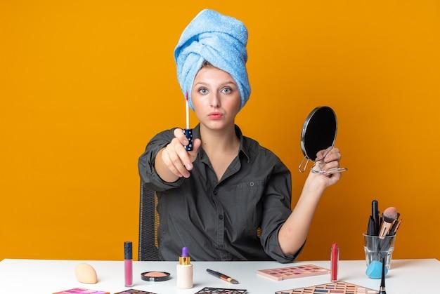 자신감 있는 아름다운 여성이 화장 도구로 머리를 감싼 테이블에 앉아 있다