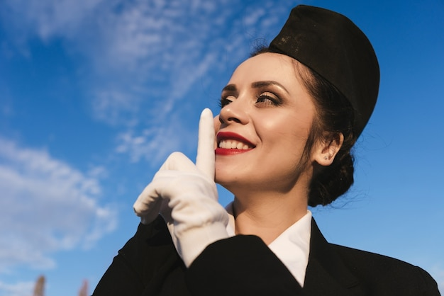 Confident beautiful woman stewardess in the form put a finger to her lips, under the blue sky