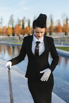 Confident beautiful woman stewardess in uniform with suitcase waiting for her flight