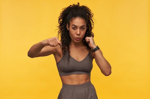Уверенная красивая молодая фитнес-женщина делает упражнения по боксу с тенью и смотрит на фронт, изолированный над желтой стеной
