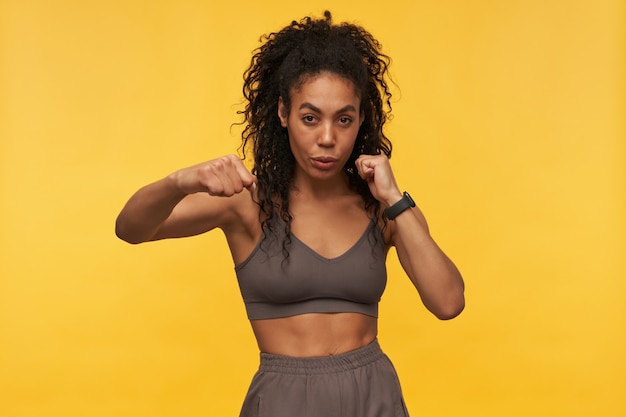 Confident beautiful young fitness woman doing shadow boxing exercises and looking at front isolated over yellow wall