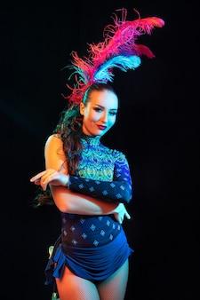 自信がある。カーニバルの美しい若い女性、ネオンの光の中で黒い壁に羽を持つスタイリッシュな仮面舞踏会の衣装。広告のコピースペース。休日のお祝い、ダンス、ファッション。お祝いの時間、パーティー。