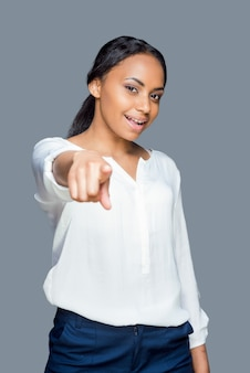 Confident beauty choosing you. waist up of attractive young african woman showing her thumb up and smiling while standing against grey background