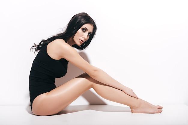 자신감 있는 아름다움. 흰색 배경 앞에 앉아 카메라를 보고 검은 수영복에 매력적인 젊은 여자의 측면 보기