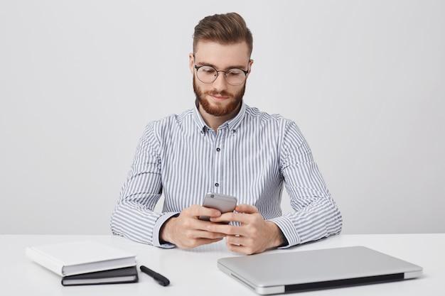 トレンディな髪型の自信を持っているひげを生やした男性フリーランサーがリモートで動作し、集中的な表現でスマートフォンの画面を見て、オンラインで通信し、白い壁に分離されたオフィスで無料のwi fiを楽しんでいます