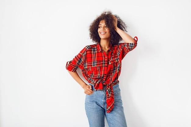 自信を持って黒の女の子が白い背景にポーズします。赤い市松模様のシャツを着ています。ブルージーンズ。