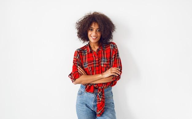 Уверенно черная девушка позирует на белом фоне. одет в красную клетчатую рубашку. синие джинсы.
