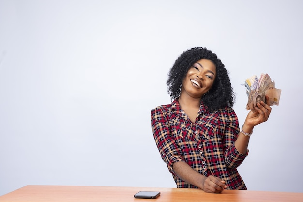 Уверенная черная дама сидит и держит пачку денег на изолированном фоне
