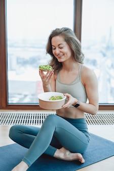 Уверенная блондинка улыбается женщина, наслаждаясь здоровой пищей, сидя в тренажерном зале на ковре, одетом в спортивную форму возле окна.