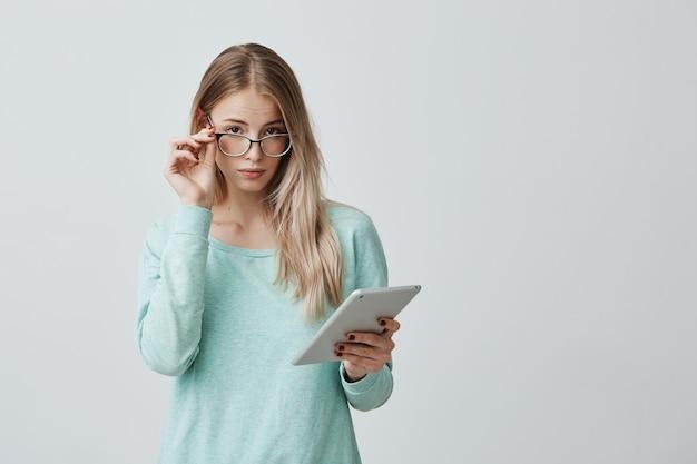 スタイリッシュなアイウェアで自信を持って金髪の女性起業家は、灰色の壁にタブレットで立って、新しいプロジェクトの開発に取り組んでいます。メガネの若い先生は現代の技術を使用しています