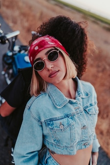 Confident blonde female wearing a denim outfit and posing on a motorcycle with her partner
