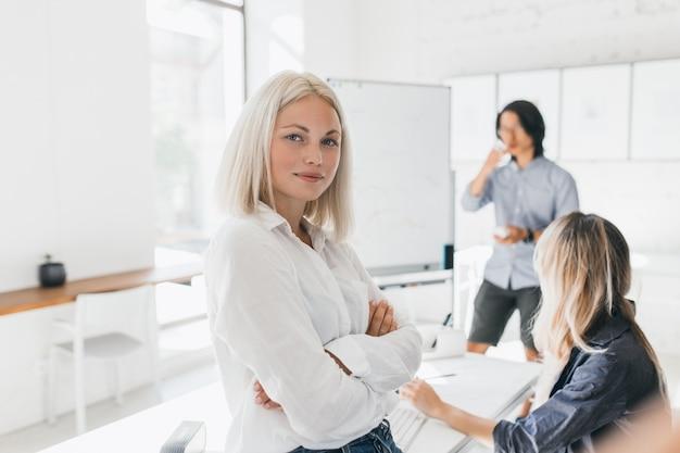 Fiduciosa ragazza bionda in camicetta in piedi con le braccia incrociate in ufficio con grande lavagna a fogli mobili