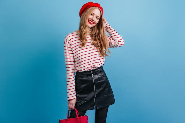 ハンドバッグを保持している黒いスカートで自信を持ってブロンドの女の子。青い壁に立っているベレー帽のうれしそうな女性。