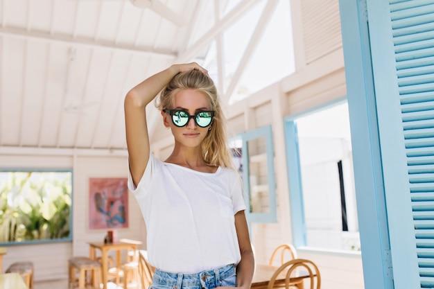 サングラスでポーズをとっている間彼女の髪に触れる自信のあるブロンドの女の子。白いtシャツでファッショナブルな日焼けした若い女性の屋内写真。