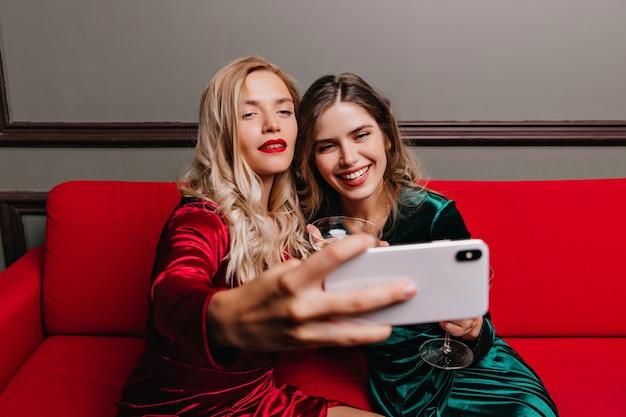 Fiduciosa ragazza bionda utilizzando il telefono per selfie alla festa. signore caucasiche che bevono champagne sul divano.