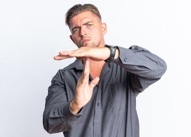 자신감이 금발의 잘생긴 남자는 복사 공간이 있는 흰색 벽에 격리된 시간 초과 표시를 몸짓으로 표시합니다.