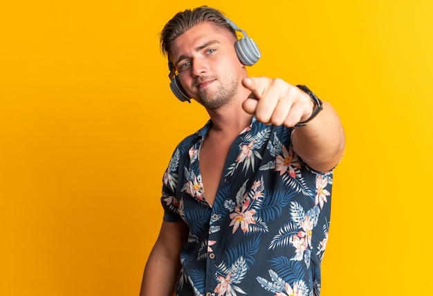 Confident blonde handsome man on headphones pointing at front