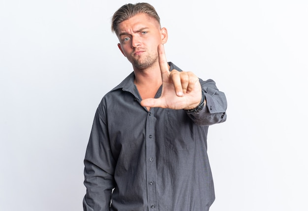 Confident blonde handsome man pointing up