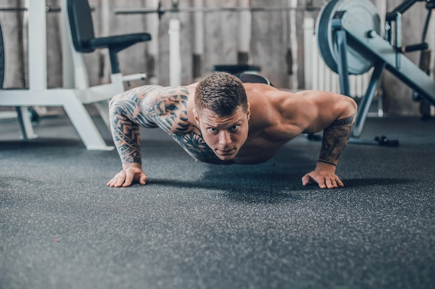 Confident bodybuilder makes push-ups in the fitness room . photo with copy space