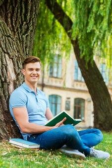 自信のある本の虫。自信を持って本を読んで、芝生の上や大学の建物の前に座って笑っている男子学生