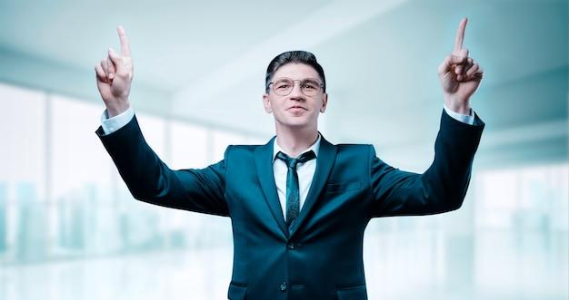 비즈니스 정장에 자신감있는 보스는 사무실에서 승리를 축하합니다. 팔을 들고 그는 웃고있다. 비즈니스 동기.