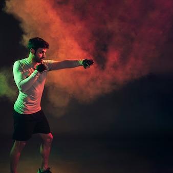 Confident boxer in dark smoke in studio