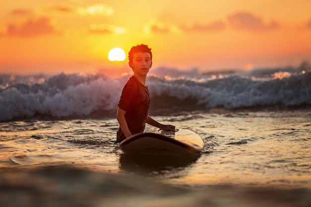 Confident boy carrying surfboard while standing at seaside in sunset