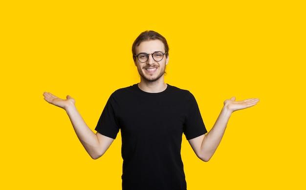 균형을 모방하는 손바닥에 두 가지를 비교하는 긴 머리와 안경을 가진 자신감있는 소년