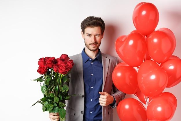로맨틱 한 데이트에가는 양복에 자신감이 남자 친구, 카메라에 윙크, 빨간 장미 꽃다발을 들고 하트 풍선 근처에 서서 윙크, 흰색 배경 위에 서.