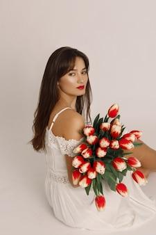 Уверенная брюнетка женщина с красными губами, одетая в белое платье