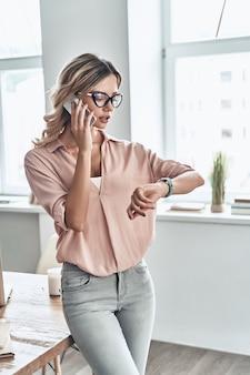 Уверенный бизнес-эксперт. красивая молодая женщина разговаривает по мобильному телефону и проверяет время, стоя в современном офисе