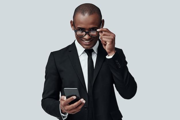 자신감 있는 비즈니스 전문가. 스마트 폰을 사용하고 회색 배경에 서서 웃고 있는 정장 차림의 매력적인 젊은 아프리카 남자