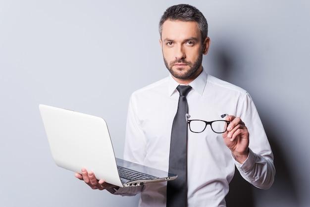 자신감 있는 비즈니스 전문가. 회색 배경에 서 있는 동안 셔츠와 넥타이에 노트북과 안경을 들고 있는 자신감 있는 성숙한 남자
