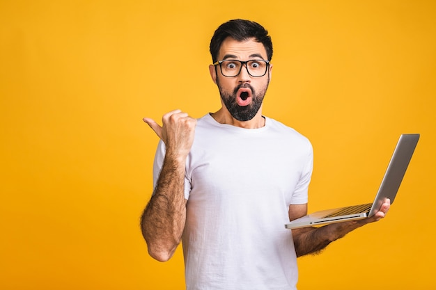 Confident business expert. confident young handsome bearded man in casual holding laptop and shocked amazed while standing over isolated yellow background.
