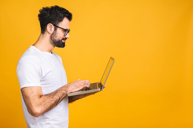 Confident business expert. confident young handsome bearded man in casual holding laptop and smiling while standing over isolated yellow background.