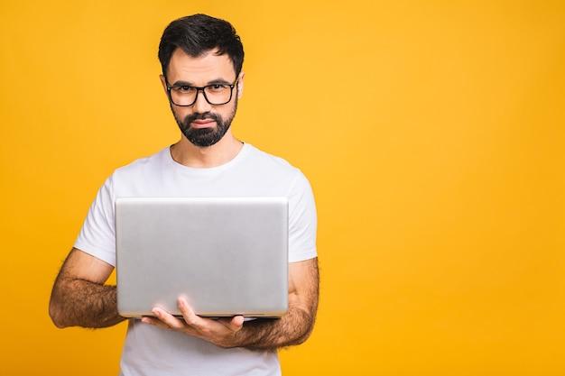 Уверенный бизнес-эксперт. уверенный молодой красивый бородатый мужчина в случайном холдинге компьтер-книжка и улыбается, стоя на изолированном желтом фоне.