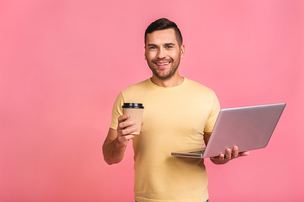 Confident business expert. confident young handsome man in casual holding laptop and smiling. drinking coffee to go.