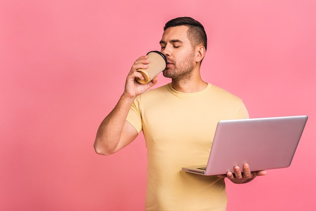 Confident business expert. confident young handsome man in casual holding laptop and smiling while. drinking coffee to go.