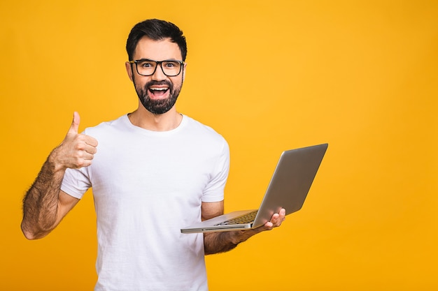 Confident business expert. confident young handsome man in casual holding laptop and smiling while standing isolated over yellow background. thumbs up.