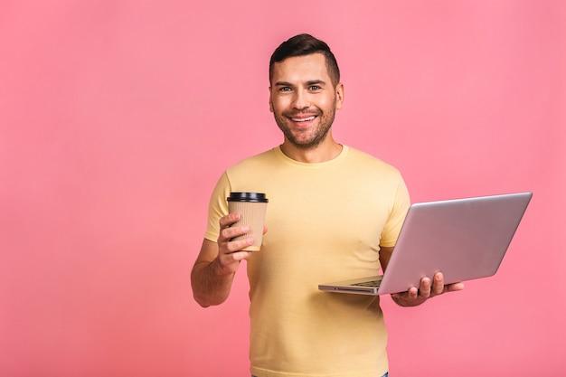 Уверенный бизнес-эксперт. уверенно молодой красивый человек в случайном холдинге компьтер-книжка и улыбается. пить кофе с собой.
