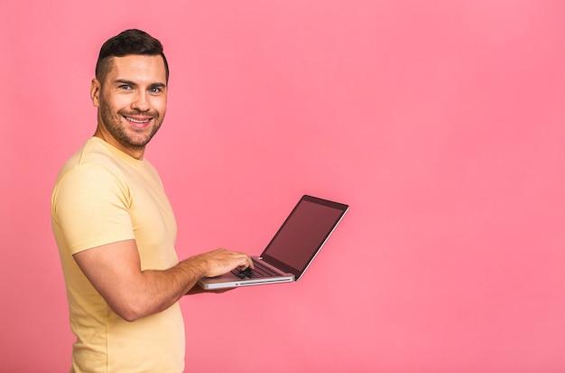 自信のあるビジネスエキスパート。ラップトップを持って笑顔でカジュアルに自信を持って若いハンサムな男