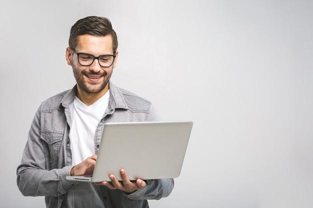 自信のあるビジネスエキスパート。ラップトップを押しながら白い背景に立っている笑顔のシャツで自信を持って若いハンサムな男
