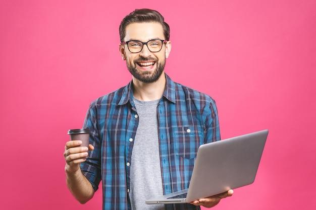 Уверенный деловой эксперт. уверен молодой красавец с кофе в рубашке, держа ноутбук и улыбается