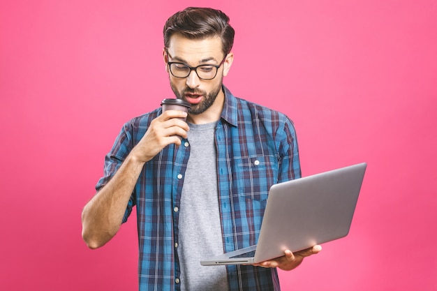 Уверенный деловой эксперт. уверен, молодой красавец с кофе в рубашке, держа ноутбук