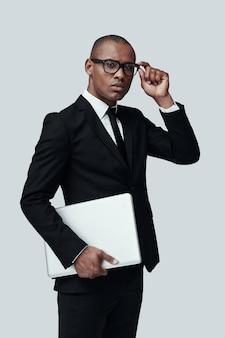 자신감 있는 비즈니스 전문가. 정장 차림의 젊은 아프리카 남자는 안경을 조정하고 회색 배경에 서 있는 동안 카메라를 보고 있습니다.