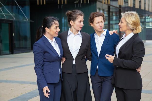 自信を持ってビジネスの女性が屋外で一緒に立って、抱き合ったり話したりします。市で会議のスーツを着ているビジネスウーマン。女性チームとチームワークの概念