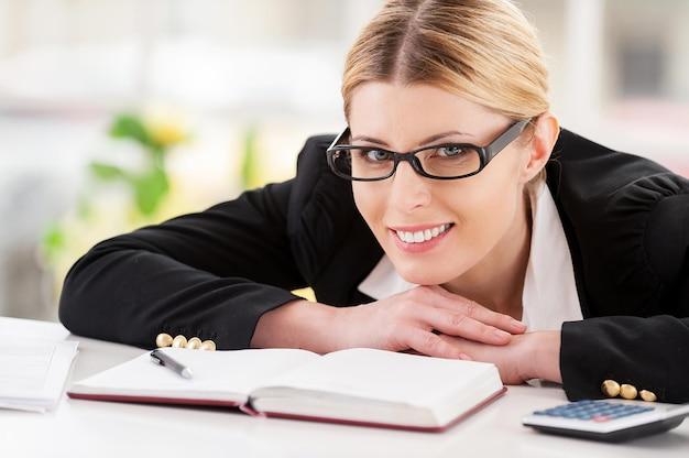 Уверенная бизнес-леди. красивая зрелая женщина в формальной одежде смотрит через плечо и улыбается, сидя на своем рабочем месте