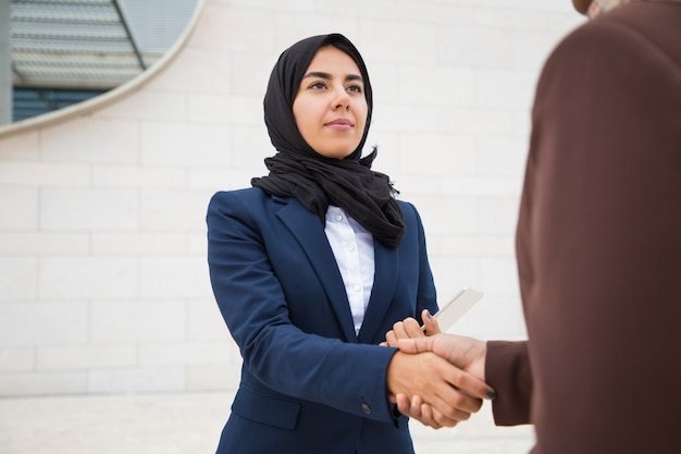 Confident business lady meeting and thanking colleague outside