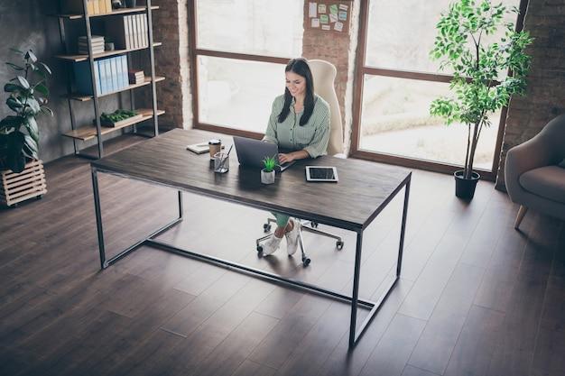 Уверенная бизнес-леди сидит за столом с ноутбуком в современном офисе