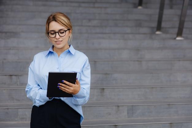 금발 머리 서 사무실 센터와 디지털 태블릿에 노력과 자신감 비즈니스 아가씨. 거리에서 작업을 위해 현대 가제트를 사용하는 안경에 젊은 여자.